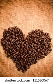 Heart sign by coffee bean on burlap texture