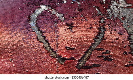 Heart silhouette on sequin fabric. Red and silver two-sided sequins background. Shiny glitter texture. Bright brilliant backdrop. Fashion glamorous textured scales. Love concept. Valentine's Day decor