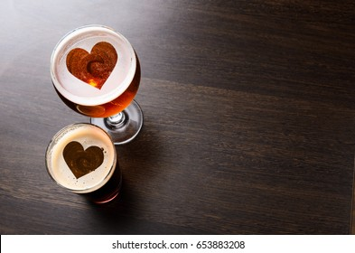Heart silhouettes in two glasses of fresh beer on pub table, view from above