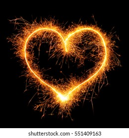 Heart from sparkler on black background. Design element for wedding or Saint Valentine card. Love symbol Valentine's Day from bengal fire - using camera with slow shutter speed.