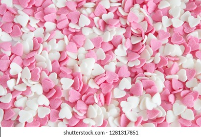 A lot of heart sprinkles  as a background. Sugar sprinkle dots, decoration for cake and bakery, Colorful sprinkles on a white  background, top view with copy space.