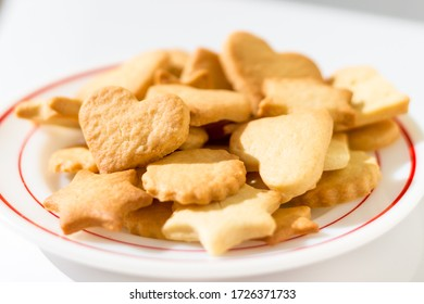 Heart, star and flower shaped homemade butter cookies on a dish in beautiful sunlight