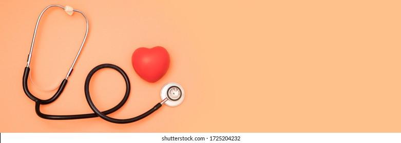 Ein Herz mit Stethoskop auf rotem Hintergrund