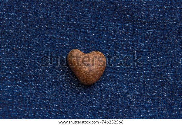 A heart of stone. Denim background.
