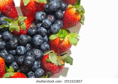 heart of strawberries and blueberries on a white background with space for text