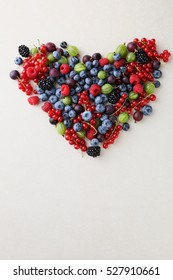 Heart with summer berry and fruits, food background