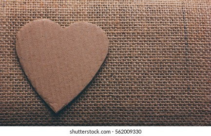 the heart symbol cut out from cardboard on burlap closeup with space for your text