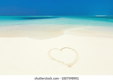 Heart symbol drawing on white sandy beach close to sea, travel concept and romantic card, toned image