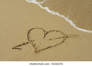 A heart symbol drawn in the sand.