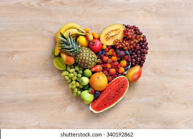 Heart symbol. Fruits diet concept. Healthy eating concept / food photography of heart made from different fruits on wooden table. High resolution product.