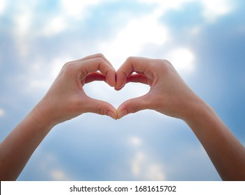 Heart symbol from hands on the blue sky background, Concept for Love or Health.