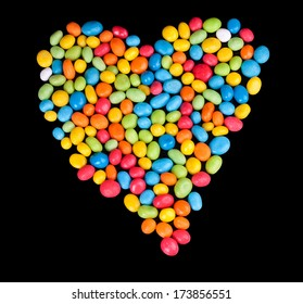 Heart symbol laid out from colorful candies isolated on a black background