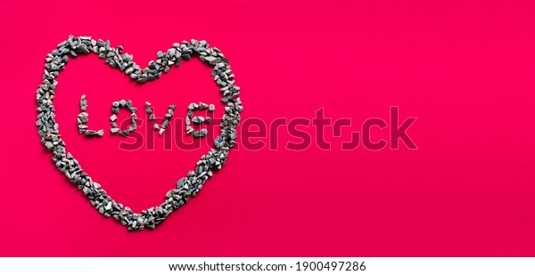 The heart symbol and the letter LOVE in the heart are made of small stones or pebbles placed on a red background. It is a concept of the day of love or Valentine's Day. Copy space, top view, closeup.