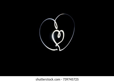 Heart symbol as long exposure light painting photography. Abstract neon light on a black background.
