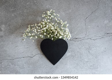 Heart symbol made of flovers and leaves. Male hand holding one last flower.