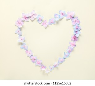Heart symbol made of flower petals,yellow background