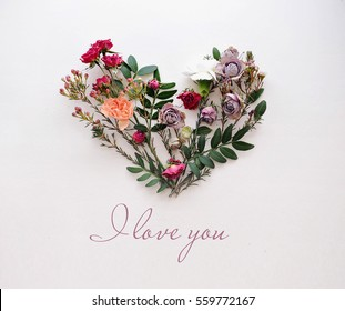 Heart symbol made of flowers and leaves on white background with texting I love you