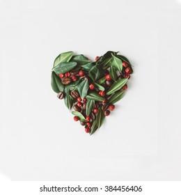 Heart symbol, made of leaves berries and coffee beans, broken in half.