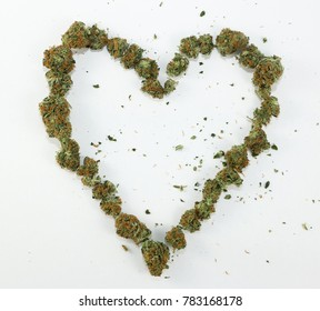 A heart symbol made with real marijuana on white.