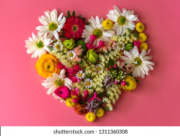Heart symbol made of spring flowers on pink background. Flat lay, top view.