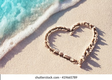 Heart Symbol On a Sand Of Beach With Soft Blue Wave On Background