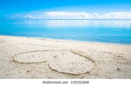 Heart symbol on sandy beach with bule sky