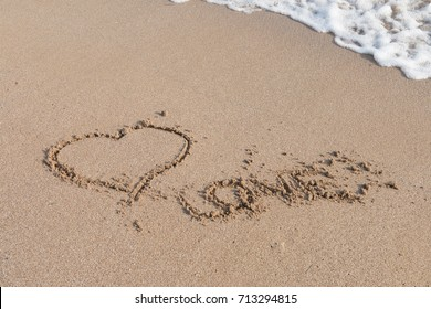 Heart symbol in the sand by the ocean