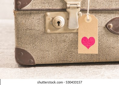 Heart tag on old vintage suitcase. Concept of travel with luggage, tourism and holiday destination.