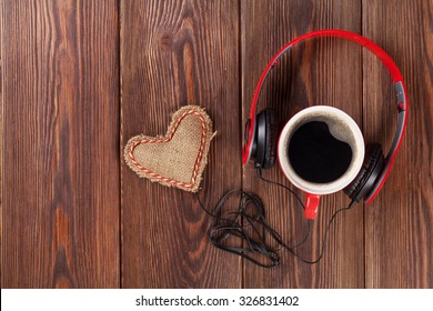 Heart toy with headphones and coffee cup on wooden table with copy space. Valentine's day concept.