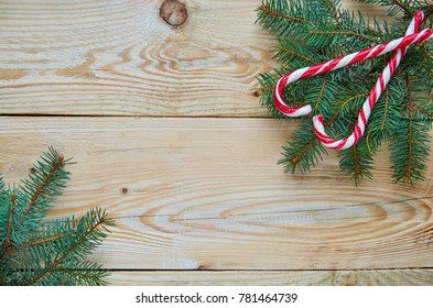 Heart of two red candy cones on the Christmas tree braches on the top right corner. New year or Valentines day sweets decorations with fir branches on the brown wooden background with free copy space