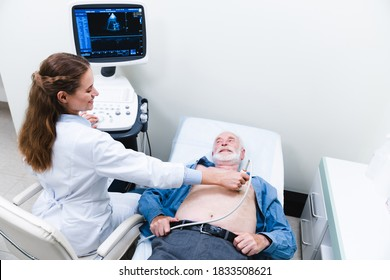 Heart ultrasound examination performed by woman doctor with smiling aged patient