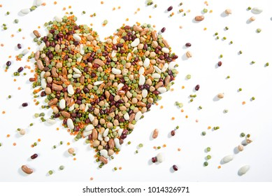 Heart of various legumes and scattered legumes, on a white background