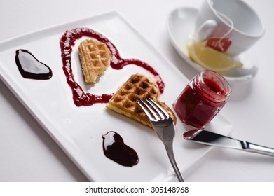 A heart waffle on a heart shaped berries sauce and two chocolate sauce hearts on a square plate  on a white background,  tea cup with lemon in the background. Selective focus.