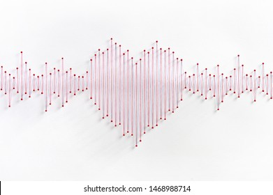 Heart waves concept. Network of pins and threads in the shape of waves symbolising love, the language of the heart.
