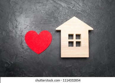 Heart and wooden house on a gray concrete background. The concept of a love nest, the search for new affordable housing for young couples and families. Favorite house, homesickness.