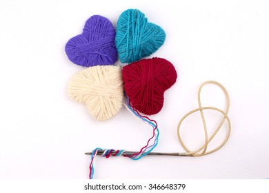 heart wool yarn in coils with knitting needles