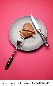 Heartbreaker concept image: heart shaped cookie on plate with fork and knife over pink background