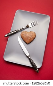 Heartbreaker concept image: heart shaped cookie on plate with fork and knife over red background