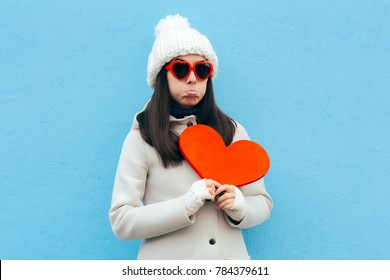 Heartbroken Sad Upset Girl Holding a Heart on Blue Background. Girl feeling blue sad after breakup in time for Valentine's Day