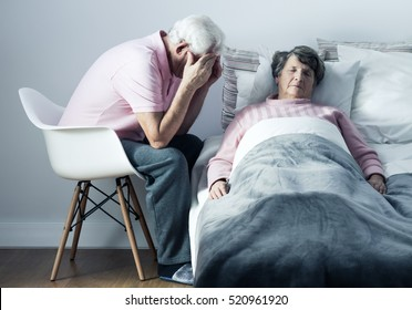 Heartbroken senior man sitting on a chair close to his ill wife lying on a bed