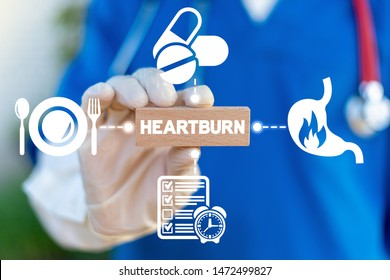 Heartburn Acid Reflux Disease Stomach Symptoms Health Care concept. Doctor hold wooden block with heartburn word and arround gastric icons.