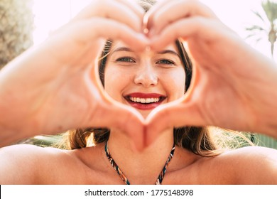 Hearth and love concept with young beautiful caucasian girl do symbol with hands under the summer sunlight - life and lifestyle with cheerful happy attractive woman outdoor