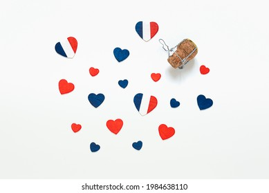 Hearts in the colors of the French flag and a french champagne bottle cork on a light background, top view, Bastille Day and French National Day concept