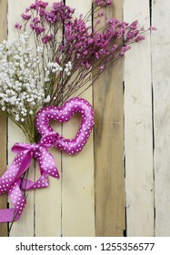 Hearts and flowers in pink with copy space for Valentine's Day, Mother's Day, wedding or engagement party. A mixture of baby's breath and broom bloom with a fun, polka dot heart shape on wood