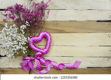 Hearts and flowers in pink good for Valentine's Day, Mother's Day, wedding or engagement party. A mixture of baby's breath and broom bloom with a fun, polka dot heart shape on a wooden background