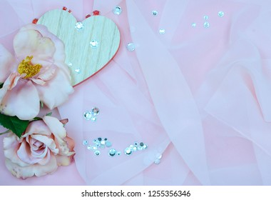 Hearts and flowers in shades of pink with copy space, good for Valentine's Day, wedding or engagement party. Silk roses, a wooden heart and sparkly gems all on a soft, silky background