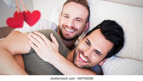 Hearts hanging on a line against happy gay couple lying on bed