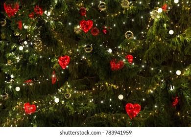 Hearts, lights and shiny balls decorating christmas tree