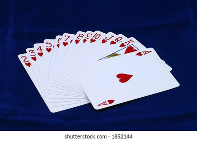 Hearts playing card suit fanned out on a blue background.  Ace on top.