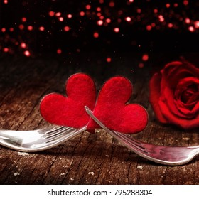 Hearts, rose and forks in front of bokeh for Valentine's Day